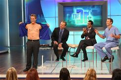 Danny Cahill, winner of 'The Biggest Loser,' appears on The Doctors TV series to reveal his new body. From left, doctors Andrew Ordon, Ritu Chopra and Travis Stork applaud.