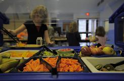 "A student picks from the ""Five a Day Bar,"" including locally grown fruits and vegetables at the Fisher Hill School cafeteria in Orange, Mass., in 2008."