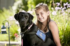 Ashley Bogdan, 13, sits with her service dog Bria in their Brentwood, Calif., yard. Bria is specially trained to alert Bogdan, who has diabetes, when her blood sugar is wrong.
