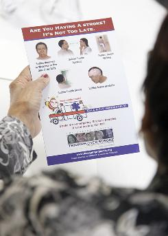 A senior reads over a refrigerator magnet with information on the signs of having a stroke and what steps they should take during a community meeting at Hattie Holmes Wellness Center in the Petworth neighborhood of Washington, D.C., Oct. 4.