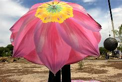 A woman shades herself from the desert sun with an umbrella in Albuquerque