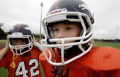 Sixth-graders Reed Hoelscher, right, and teammate Alec Jordan, wearing a new type of helmet designed to reduce the risk of concussions, wait for the second half of a youth football game to start in Richardson, Texas, in September.
