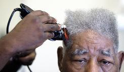 A man gets his hair cut at a barbershop in Washington, D.C.