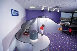 Children romp on the baggage claim slide at the Kidport in Terminal C of Boston's Logan Airport.