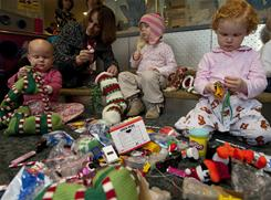 Lisa Scherber, director of patient and family programs at the Dana-Farber Children's Hospital Cancer Center in Boston helps, from left, Phoebe Davis, 3, Sophie Pettengill, 3, and Eliza, 2, stuff gifts into stockings in preparation for the center's holiday celebration, which Scherber has helped run for years.