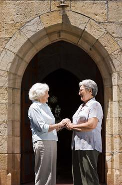 Women greet each other outside of church.