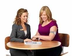 A Jenny Craig consultant works with a client wearing BodyMedia FIT Armband, which measures energy expended.