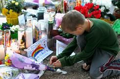 A young boy lights a candle at the makeshift memorial outside of the District Office of U.S. Rep. Gabrielle Giffords. Arizona makes it easier than most states to commit mentally ill people to psychiatric care, even against their will. But that doesn't mean that everyone gets the help they need.