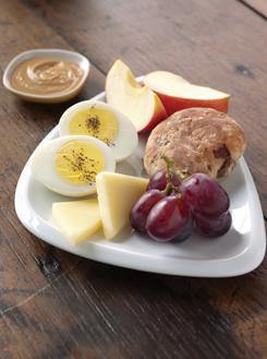 The protein artisan snack plate from Starbucks features sliced hard-boiled egg, cheese, multigrain roll and fruit.