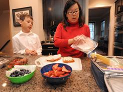 Dr. Jennifer Shu makes lunch for her son J.K. Shu is a pediatrician and an important member of the American Academy of Pediatrics.