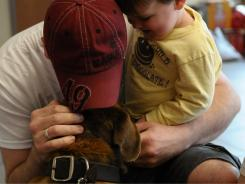 Phillip Lance and his son Jonathan are reunited with their dog Samson, who they feared was lost during the tornado.
