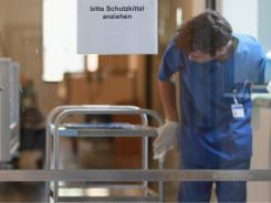 A hospital technician in Hamburg disinfects a cart in the nephrology unit, where some E. coli patients are being treated.