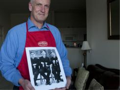 Jack Long, winner of the Father's Day recipe contest, holds a photo of his father Geoff, center, with fellow naval officers during WWII.