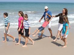 Geoff and Laura Wolf swing Emma, 5, as Adam, 11, Rachel, 12, Kyle, 9, and Sarah, 8, enjoy a walk at South Beach Park.