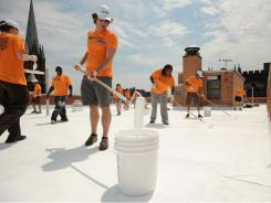 New York City volunteers paint a roof in Brooklyn as part of the Cool Roofs initiative.