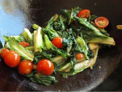 Romaine lettuce and cherry tomatoes get a wok hot oil treatment.