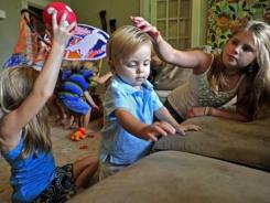 Shayli Daves strokes the hair of brother Shafer while siblings Sharayah, Shanel and Shaw play. Shafer has a disease that required the removal of both kidneys and a transplant from his mother.