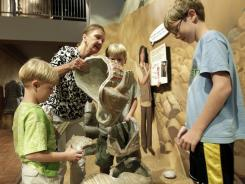 Bunny Sayler helps her grandchildren Peyton, William and Dawson Sayler rebuild a terracotta solider at the Childrens Museum in Indianapolis.
