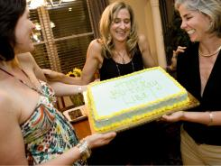 Lisa WIlkins, center, is thrilled by her birthday cake, held by friends Carrie von der Sitt, left, and Mollie Rattner.