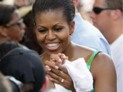First lady Michelle Obama greets onlookers during the taping of Extreme Makeover Home Edition in Fayetteville, N.C., Thursday, July 21, 2011.  (AP Photo/Gerry Broome)
