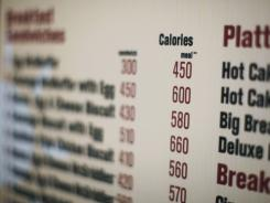 A McDonalds drive-thru menu in New York displays calorie counts for each item.