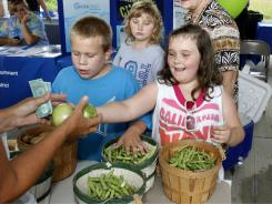 Nathan Collins, 8, left, looks on as Kelsie Collins, 7, purchases two green tomoatoes from local farmer Noreen Melton at the Jackson Co. Farmers Market in Annville, Ky.,
