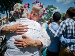 Kathy Kane, left, and Mary Kane embrace each other after saying their marriage vows in a mass wedding ceremony for gay couples.