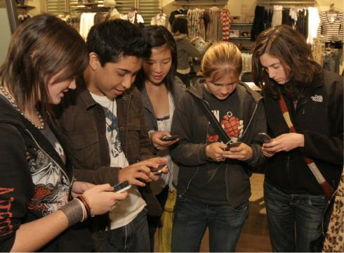Teen shoppers respond to an in-store promotion by texting in on their cell ...