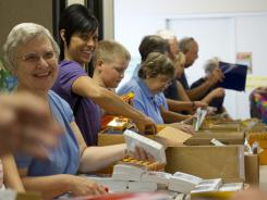 Eileen Drake, far left, and Chasi Winningham, second from left, stuff backpacks with donated materials Saturday, Aug. 6, 2011at Shepherd of the Hills United Methodist Church.