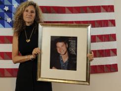 Edith Lutnick holds a picture of her brother, Gary Lutnick, in front of a quilted American flag in her office in New York City.