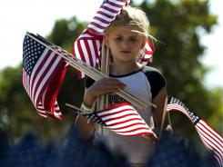 Tabitha Rogers, 8, carries flags while helping prepare for a 9/11 memorial.