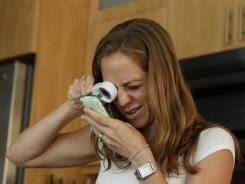 Amber McMahon, 35, reads her cellphone screen with a lighted magnifier. The Venice, Calif., wife, mother and fitness instructor was diagnosed at 18 with an inherited form of juvenile macular degeneration.