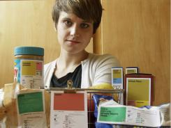 "Designer Renee Walker poses next to her food label samples. Nutrition and design experts want to overhaul the ""nutrition facts"" panel found on packaged foods to make it easier to understand what a food's value is."