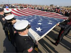 First responders hold the National September 11 Flag during a ceremony in Joplin, Mo., on Sunday, marking the end of the 50 state restoration tour. The final stitches are being placed in Joplin and then the flag will go to the National 9/11 Memorial Museum in New York.