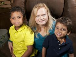 Cheri Stout-Robinson, 42, poses with her two sons, Alexander, 7, left, and Nikolas, 3 1/2, at their Oklahoma City home. Robinson says she caught a flesh-eating bacteria while in the hospital after giving birth to her second child in 2007.