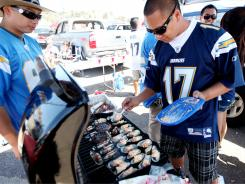Alvin Caturay cooks grilled Mussels with a spicey Mayonaise during a tailgating party in the parking lot at Qualcomm Stadium.