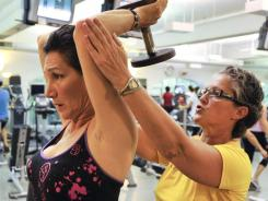 Lu-Ann Doria, left, works with trainer Laura Tiedge in Rye, N.Y. Doria, 57, began working out three years ago after recovering from breast cancer therapy.