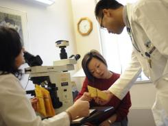 ChangBao Yuan, of Quincy, Mass., consults with pathologist  Nora Laver, M.D.FCAP, with the help of interpretor Tian Xuejun, M.D. about her Pap test at the See, Test & Treat program at Tufts Medical Center in Boston,.