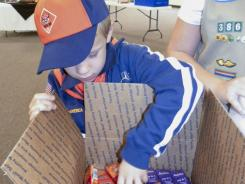 Zachary Kaiser, 7, of Cub Scout Pack 40, Girard, Ohio fills a care package for servicemen and women for Make A Difference Day at Grace Fellowship Church in Howland, Ohio.