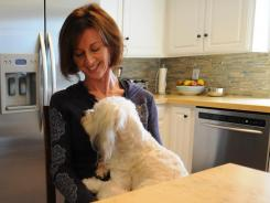 Mary Claire Orenic with the family dog Steve McQueen in the kitchen of her home in Manhattan Beach.