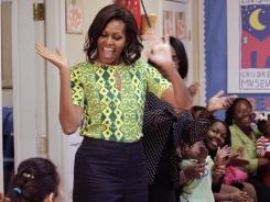 Michelle Obama waves as she arrives to visit children, parents and staff at the Royal Castle Child Development Center, as part of her 'Lets Move!' initiative.