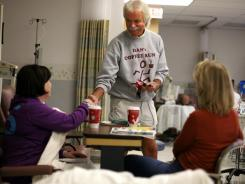 Dan Dewey, 65, of Dan's Coffee Run hands out coffee at the Michigan Cancer Institute in St. Joseph Mercy Oakland Hospital/