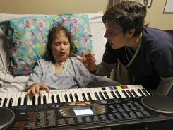 Music therapist Maegan Morrow uses a keyboard to work with Celest Powell, a cystic fibrosis patient at the TIRR Memorial Hermann Rehabilitation Hospital.