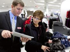 Manager Scott Parent, left, uses an iPad tablet, with a Macy's shopping app, to showcase upcoming Black Friday sales to shopper Michelle Mabardy.