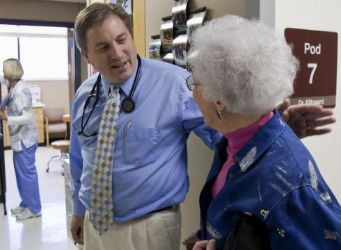 Dr. Don Klitgaard greets Muriel Bacon as her husband weighs in with a nurse.