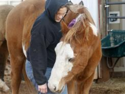 Cheri White Owl, founder of Horse Feathers Equine Rescue, is pictured with one of the 33 horses she is currently caring for, in Guthrie, Okla.