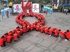 "Dozens of volunteers join a human chain in the form of a red ribbon, a symbol of ""love and care"" for HIV and AIDS carriers worldwide, at a gathering in downtown Taipei."