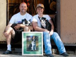 """Woody"" Bartley and his wife Deanna share a seat with  Harmony and Bowtie next to a photo of Wally, the Bartley's first dog who passed away in 2000 and was the initial motivation for them to acquire Boston terriers Chance and Bliss whom A Chance for Bliss animal sanctuary is named after."