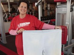 Sue Hentschel holds up the large slacks she used to wear. Henstchel lost 145 pounds.