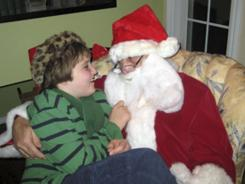 This photo provided by Darlene Borre, shows her son, Ben Borre, 10, of West Hartford, Conn., with an autism-friendly Santa Claus, Ray Lepak of Manchester, Conn.